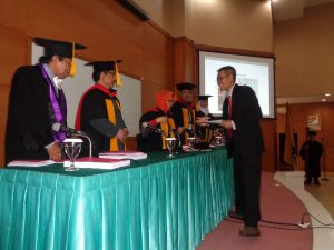 Dr. Bambang Subali, S.Pd, M.Pd menerima hasil judicium dari Ketua Sidang Promosi, Prof. Dr. Anna Permanasari, M.Si.